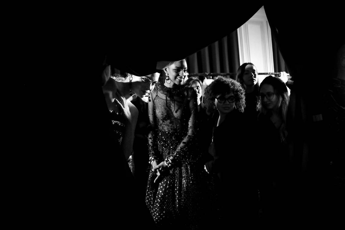 A black-and-white shot of models watching a fashion show from behind a curtain in their dressing room.