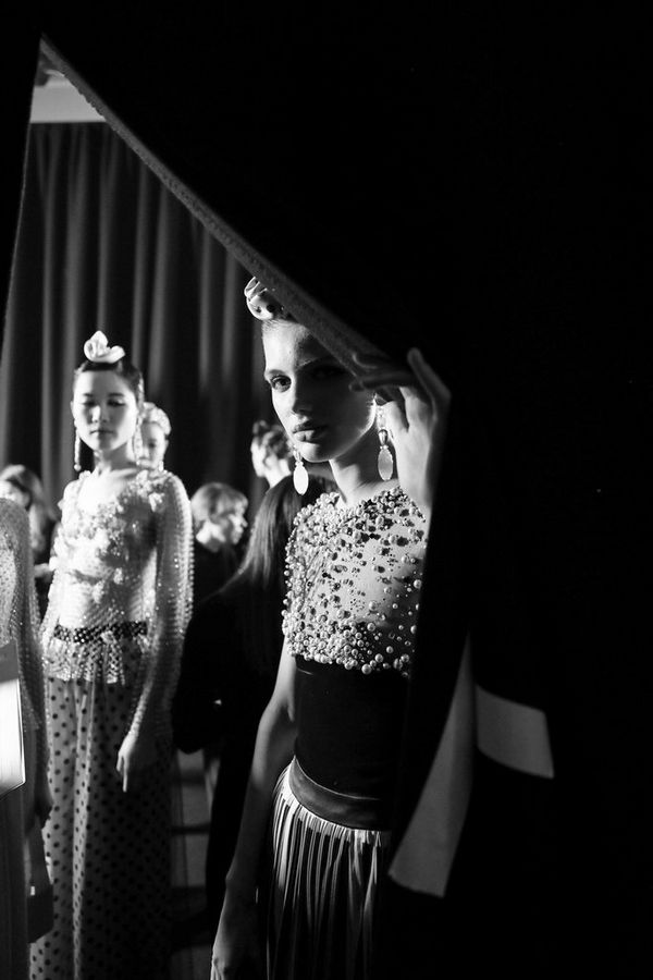 A black-and-white shot of models peering around a curtain.