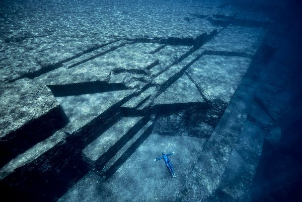 Freediver Guillaume Néry lies on the surface of an ancient underwater structure off the coast of Japan.