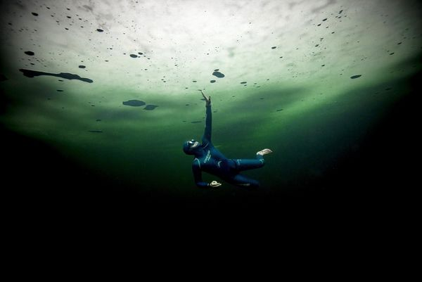 Freediver Guillaume Néry swimming under a layer of thick ice.