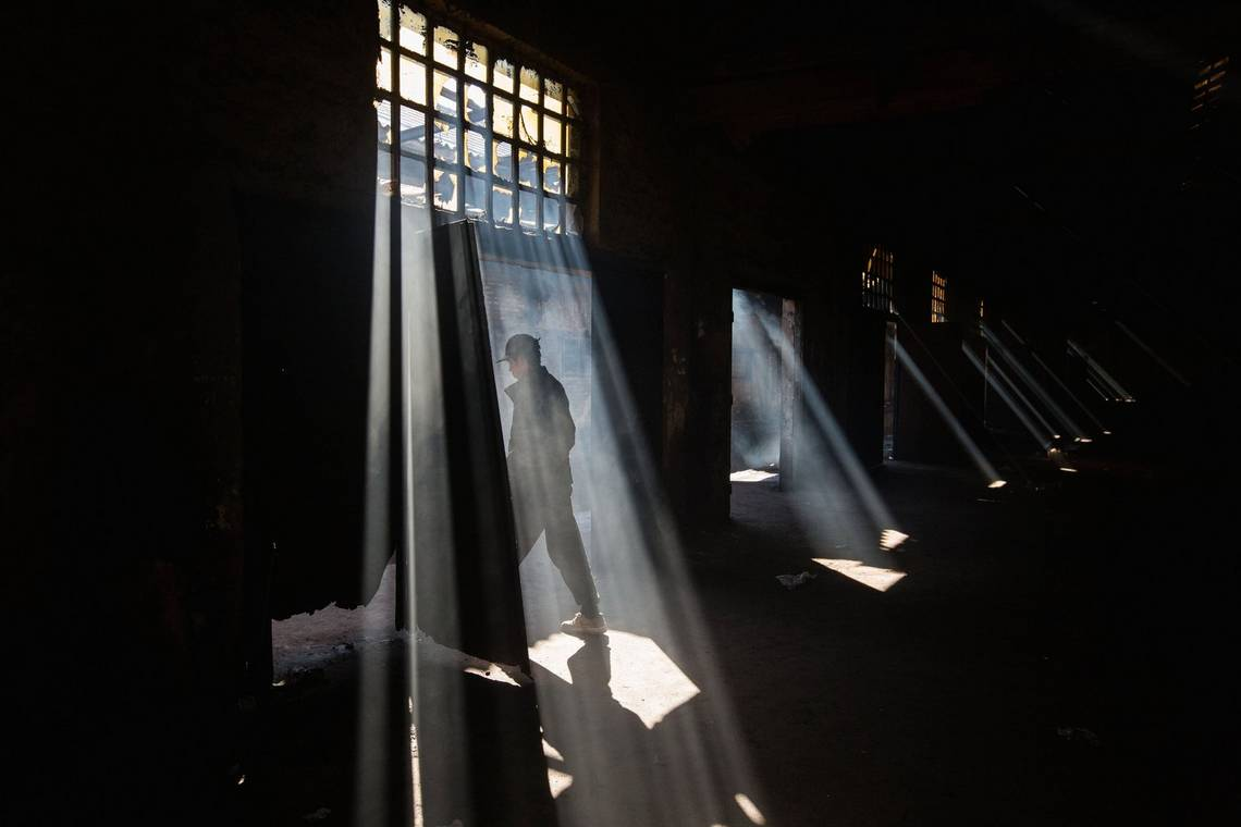 A man exits a dark warehouse as sunlight streams through the broken windows. Photo by Jędrzej Nowicki