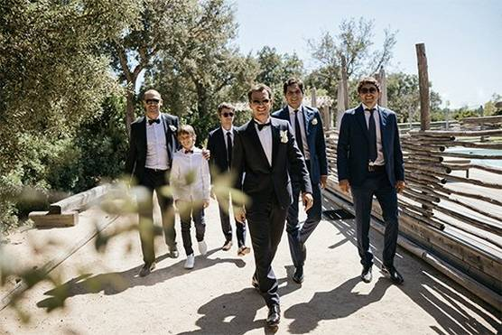 A groom and five groomsmen of various ages, most wearing sunglasses, walk towards the camera smiling broadly.