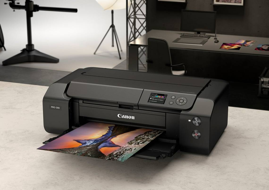 The Canon imagePROGRAF PRO-300 pro photo printer on a tabletop in a studio produces a borderless print.