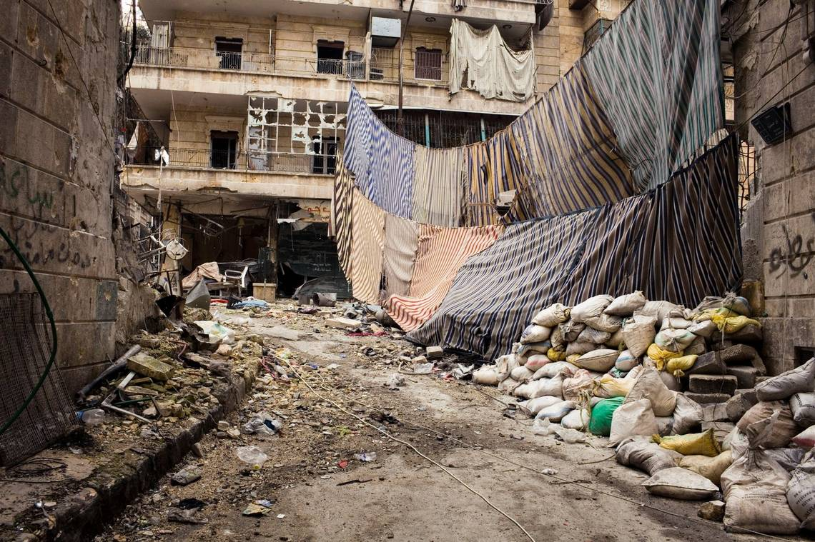 Amid the rubble of a war-torn street in southern Aleppo, sheets are strung between buildings.