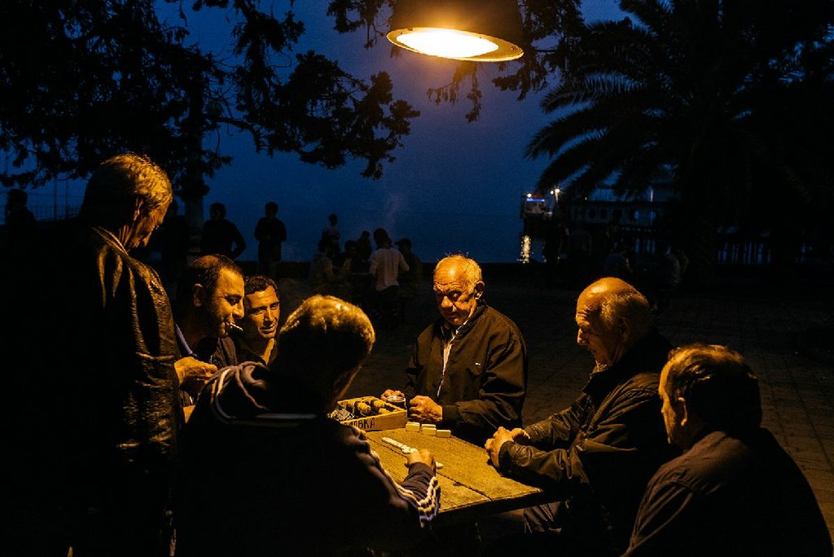 A group of Abkhaz men sit around a table near the sea playing dominoes under a lamp.