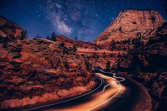 Rocky outcrops in Zion National park, Utah, USA, pictured at night. Blurred lights run along the road and the Milky Way can be seen in the sky above.