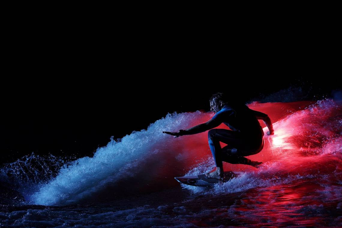 Wakesurfer Andy Schmahl rides a wave, illuminated by the the glow of an orange flare he is holding.