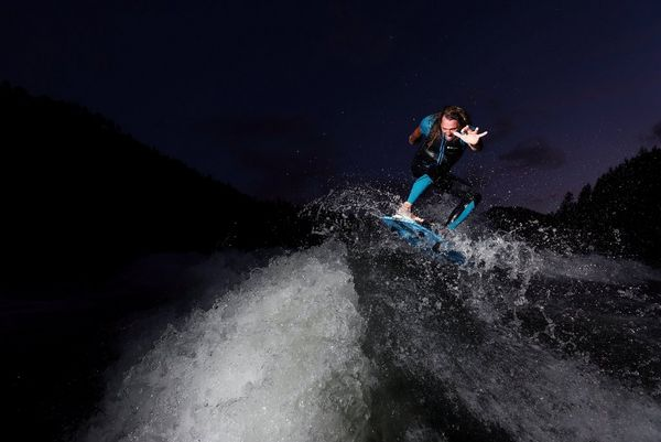 Wakesurfer Andy Schmahl rides the crest of a wave, his arms outstretched.