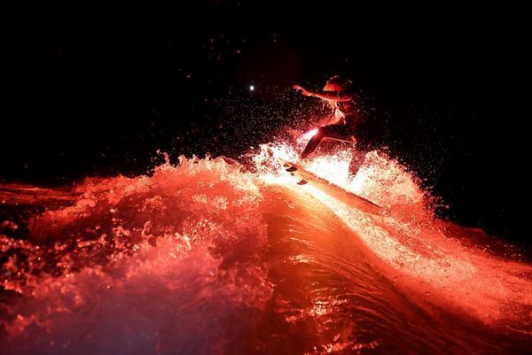 Wakesurfer Andy Schmahl rides a wave holding a red flare in his hand.