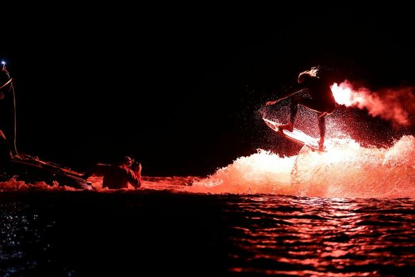 Extreme sports photographer Richard Walch stands chest deep in a lake photographing a wakesurfer carrying a flare.