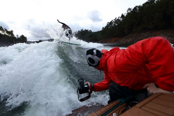 Extreme sports photographer Richard Walch leans off the back of a boat holding the camera low to capture the wakesurfer following behind.