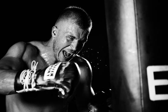 A black and white shot of a boxer throwing a punch.