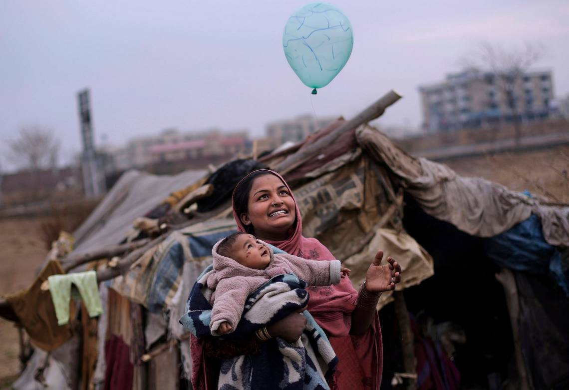A mother and daughter play with a balloon outside their tent on the outskirts of Islamabad, Pakistan.