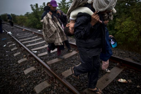 A 10-year-old Syrian refugee being carried along a railway track by her father.