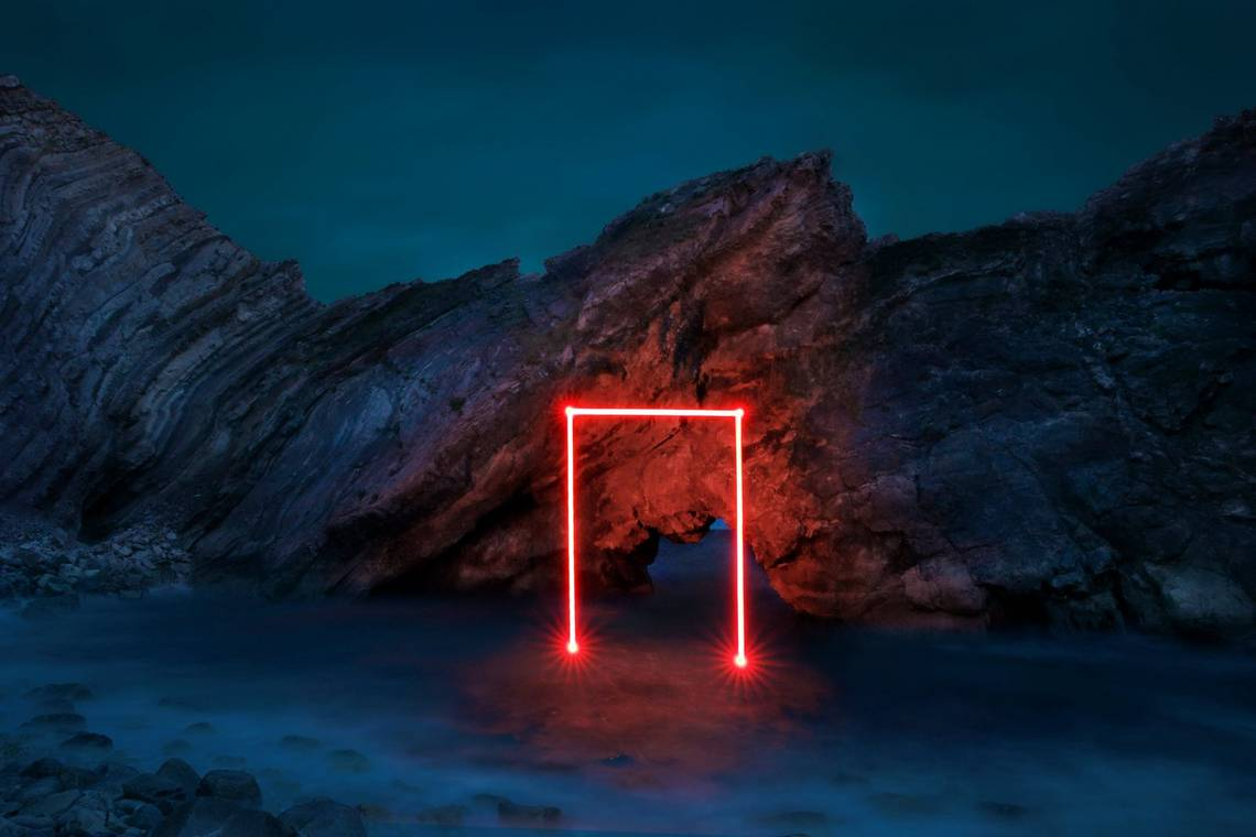 A multiple exposure image of a doorframe outlined in red light. The shape appears to emerge from the sea and is set against a rocky backdrop.