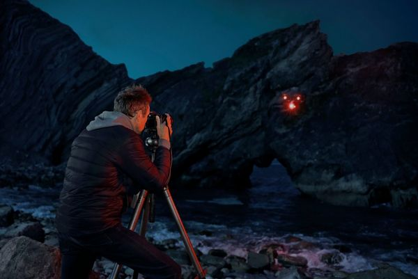 "Rob Payne photographs a rocky coastline. A drone is being used to ""paint"" red light onto the surface of the water."