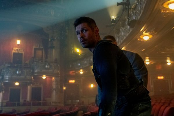 In a still from The Umbrella Academy, actors David Castañeda and Tom Hopper (behind) enter a misty theatre.