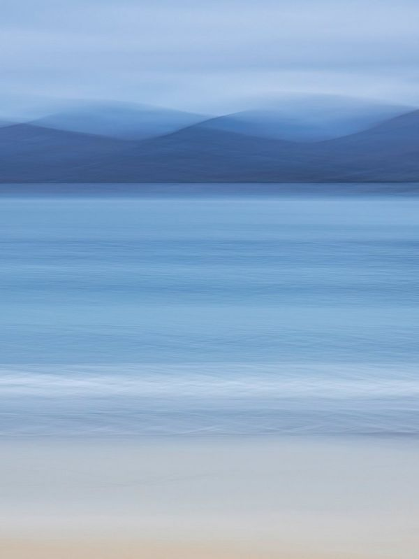 An abstract shot of a beach scene, with blurred mountains in the background.