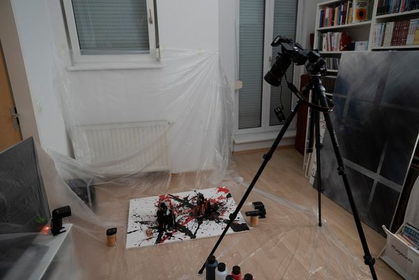 A Canon EOS R on a tripod is directed at a paint-splatter canvas on the floor. The room is covered in plastic sheeting.
