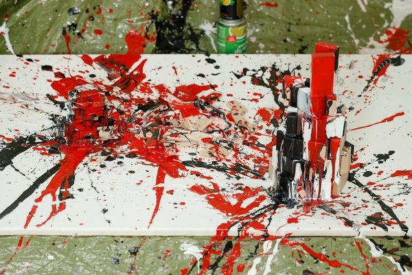 A canvas on the floor covered in splatters of red, black and white paint.