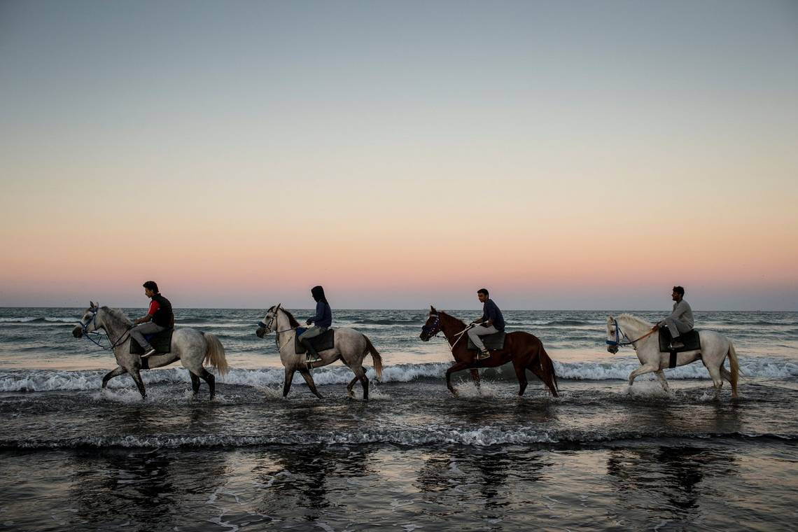 Four people riding horses through the shallow waves on a beach at sunset.