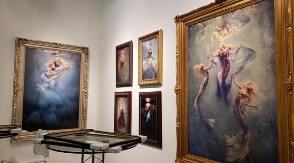 Fine art style images in ornate frames hang on the wall of a gallery.