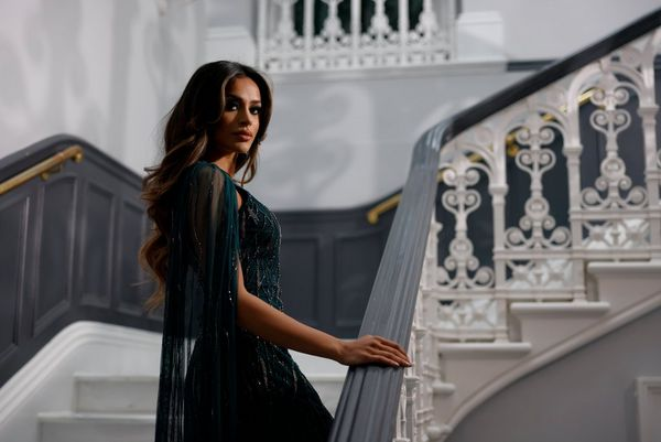 A woman in a green sequinned dress looks back over her shoulder as she climbs a staircase.
