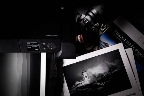 A Canon camera next to a Canon printer and a selection of black and white prints.