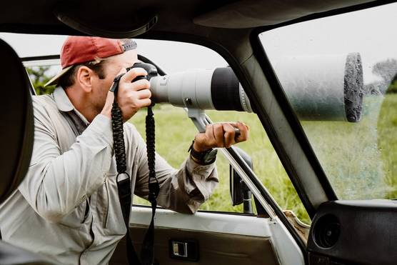 A photographer leans out of a vehicle in Murchison Falls National Park in Uganda. He is holding a Canon camera with a large telephoto lens.