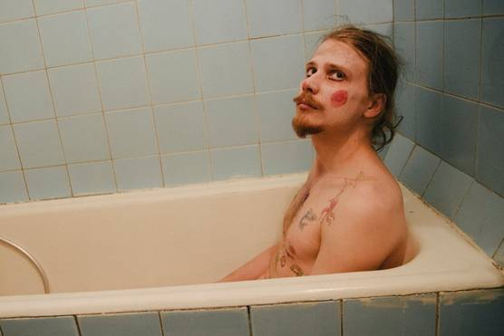A topless man sitting in a bath wearing clown make-up.