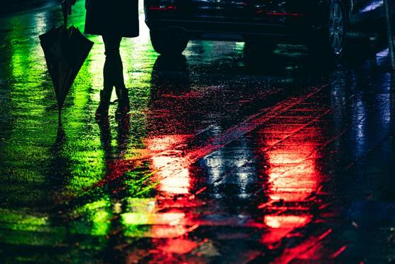 The bottom half of a woman silhouetted against a green neon reflection on the surface of a wet road. Red reflections from a car's brake lights are on the road beside her feet.