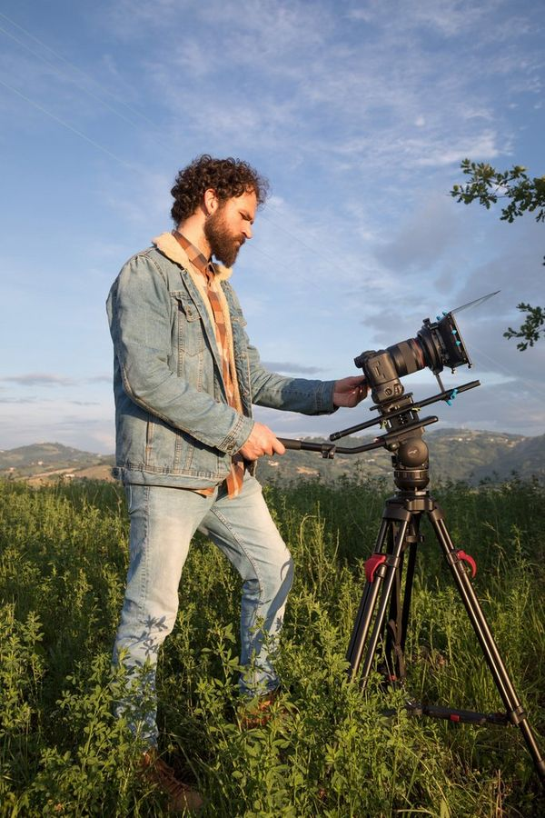 Filmmaker Ivan D'Antonio stands behind a tripod mounted with a Canon EOS R5.