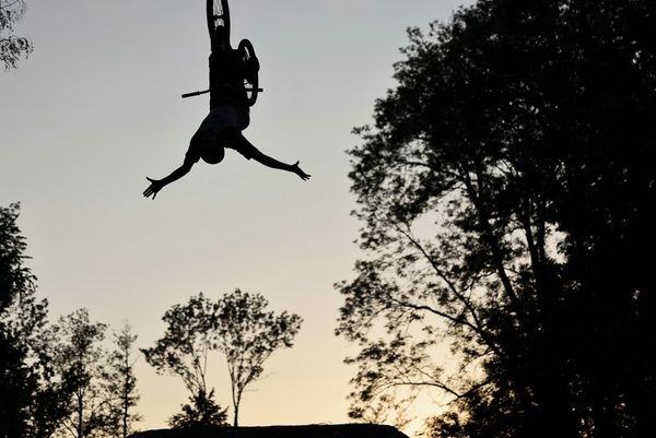 A mountain biker mid-stunt and upside down, silhouetted against the sky and framed by trees.