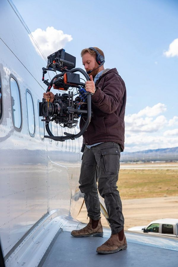 Steve Holleran with the Canon EOS C300 Mark III, standing on the wing of a plane.