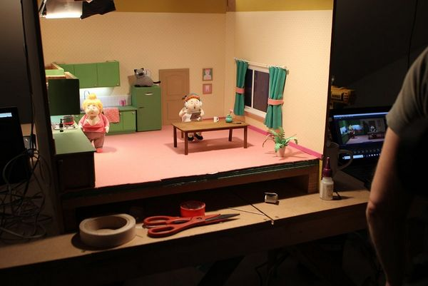 A set from No, I Don't Want to Dance! is lit, a person reviewing the photographed stop-motion footage on a screen beside the set.