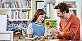 A father and daughter making papercraft flowers.