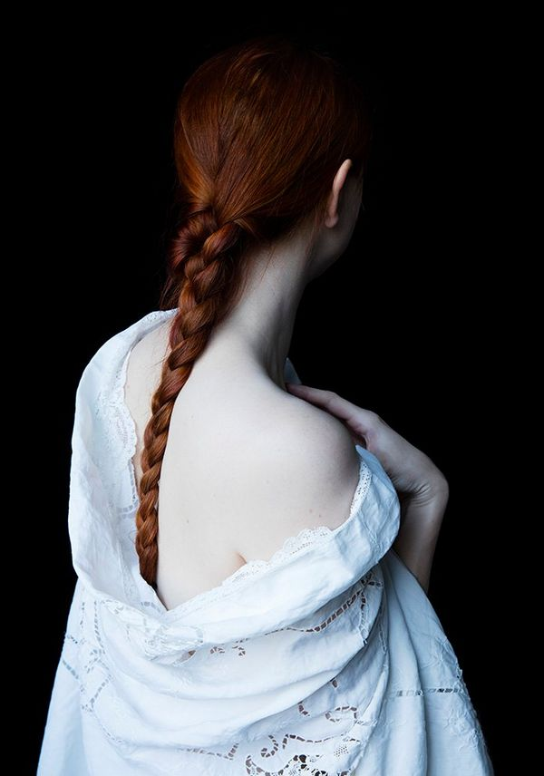 A woman with red hair tied in a plait faces away from the camera. She wears a low-backed dress that shows off her milky white skin.