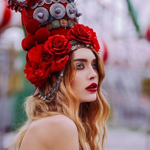 woman in red with red feather headdress