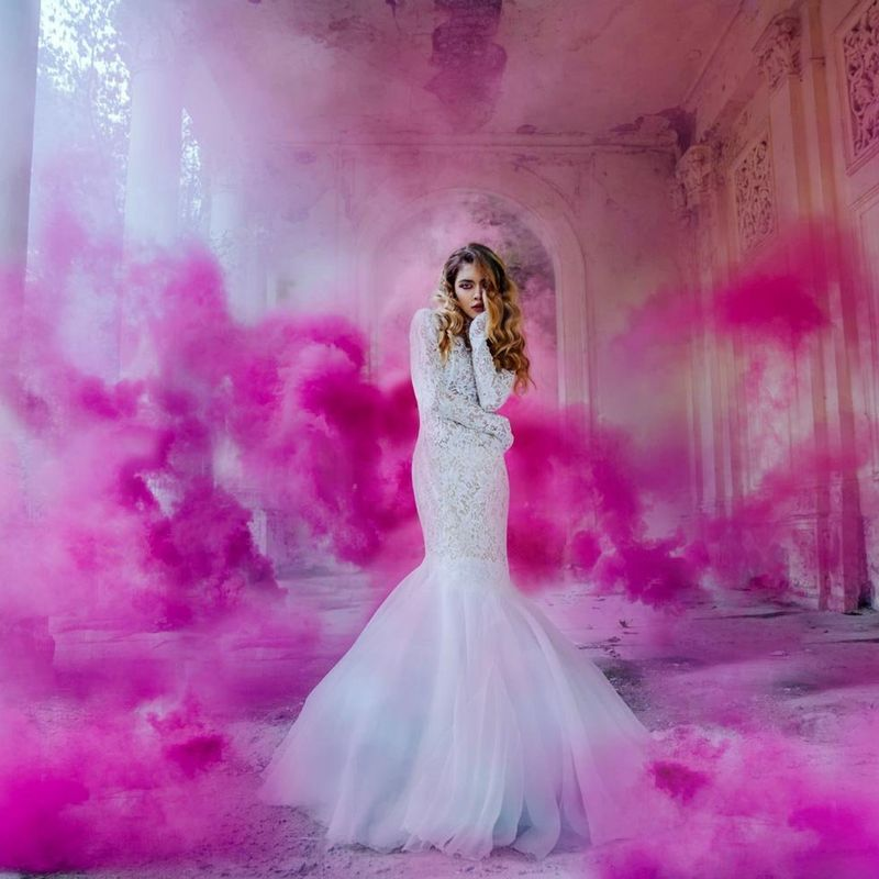 woman in white dress surrounded with pink smoke