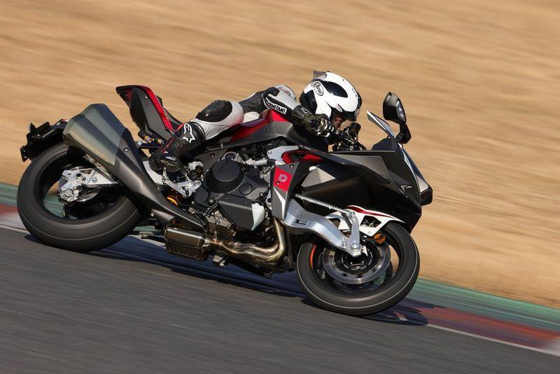 Motard penché dans un virage, sa moto paraissant très nettement, tandis que l'arrière-plan est flou.