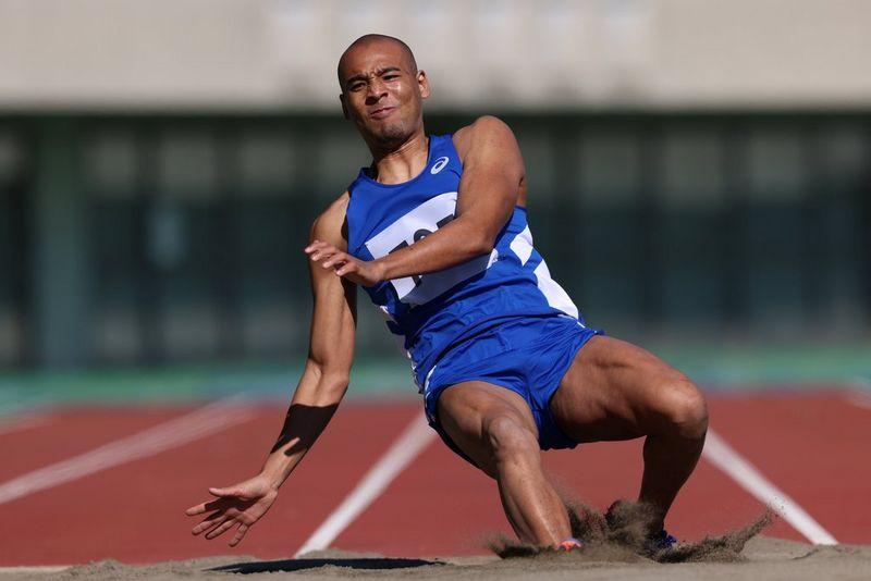 Un athlète atterrit lourdement dans un bac à sable après un saut sur une piste d'athlétisme.