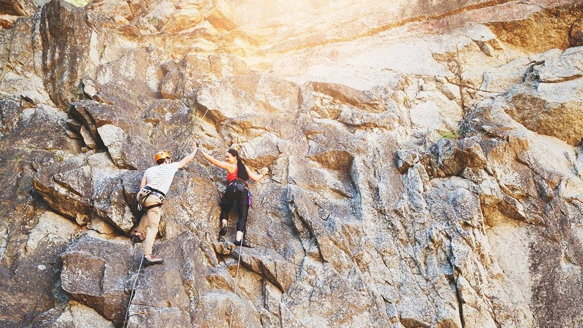 Couple high-five while rock climbing