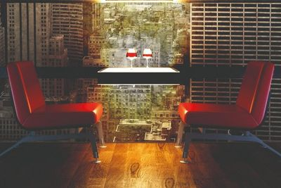 A table set with two wine glasses flanked by two red chairs in front of digitally printed wallpaper showing a cityscape