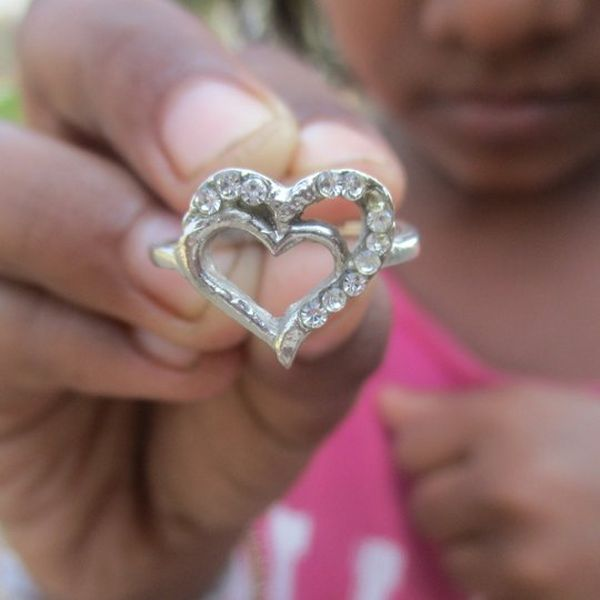A hand holding a heart-shaped silver sparkly broach