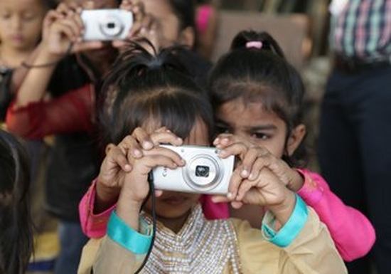 A little girl holds a Canon camera up to her face to take a picture, while behind her another little girl places her hands over hers and looks over her shoulder.