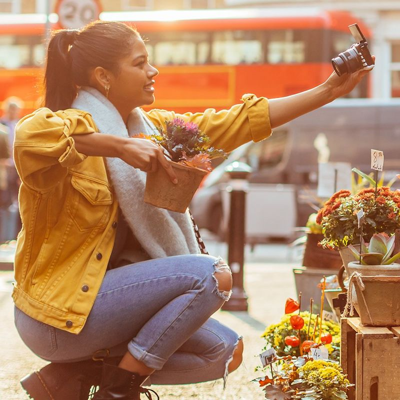 A woman crouches to street level to take a selfie with a plant, using a Canon camera.