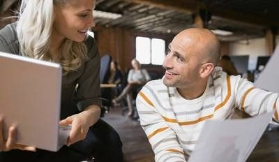 Blonde-haired woman rests a laptop in her hands as she chats to a bald man dressed in a stripy white jumper.