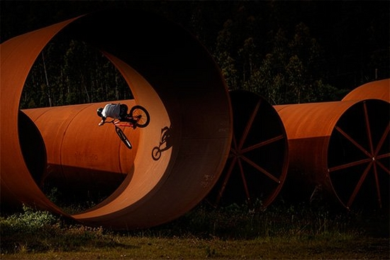 A BMX rider performs a stunt in a giant rust-coloured tube, casting a shadow against the side. Photo by Jaime de Diego.