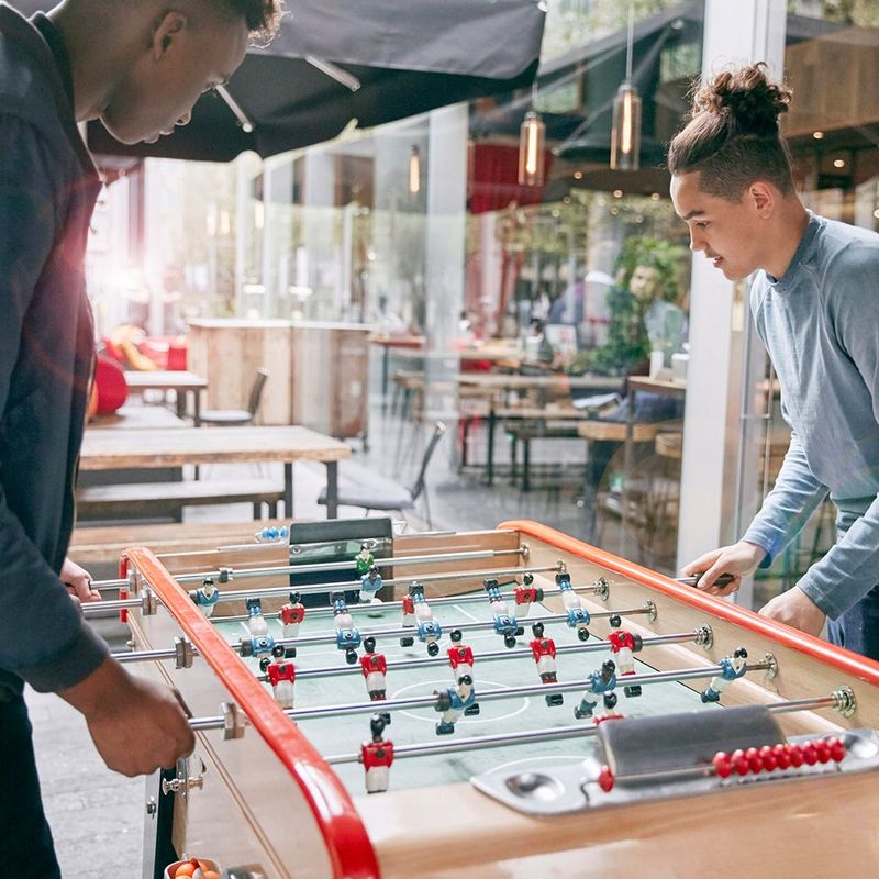 Two men play table football in a communal space