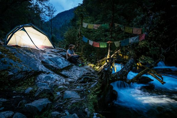 A man sits next to his tent on rocks by a waterfall. Photo by Martin Bissig.